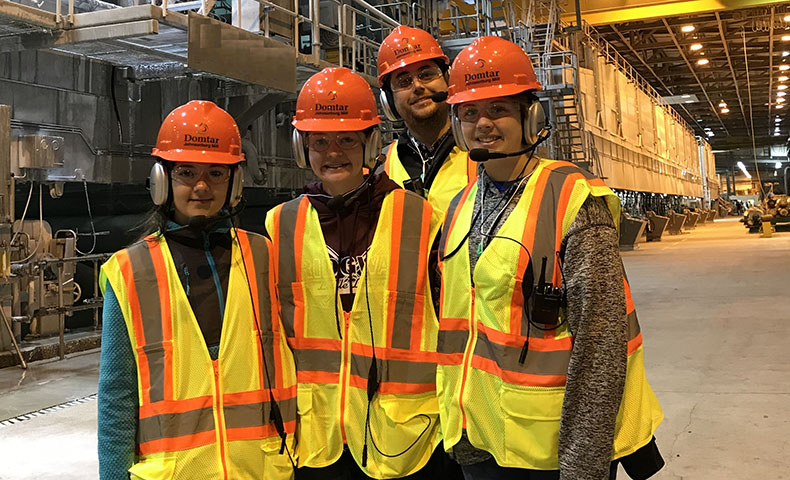 Four students with hardhats and worksite safety gear