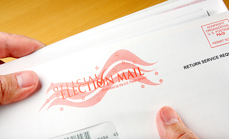hands holding a mail-in ballot