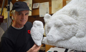 paper artist Calvin Nicholls with two of his works