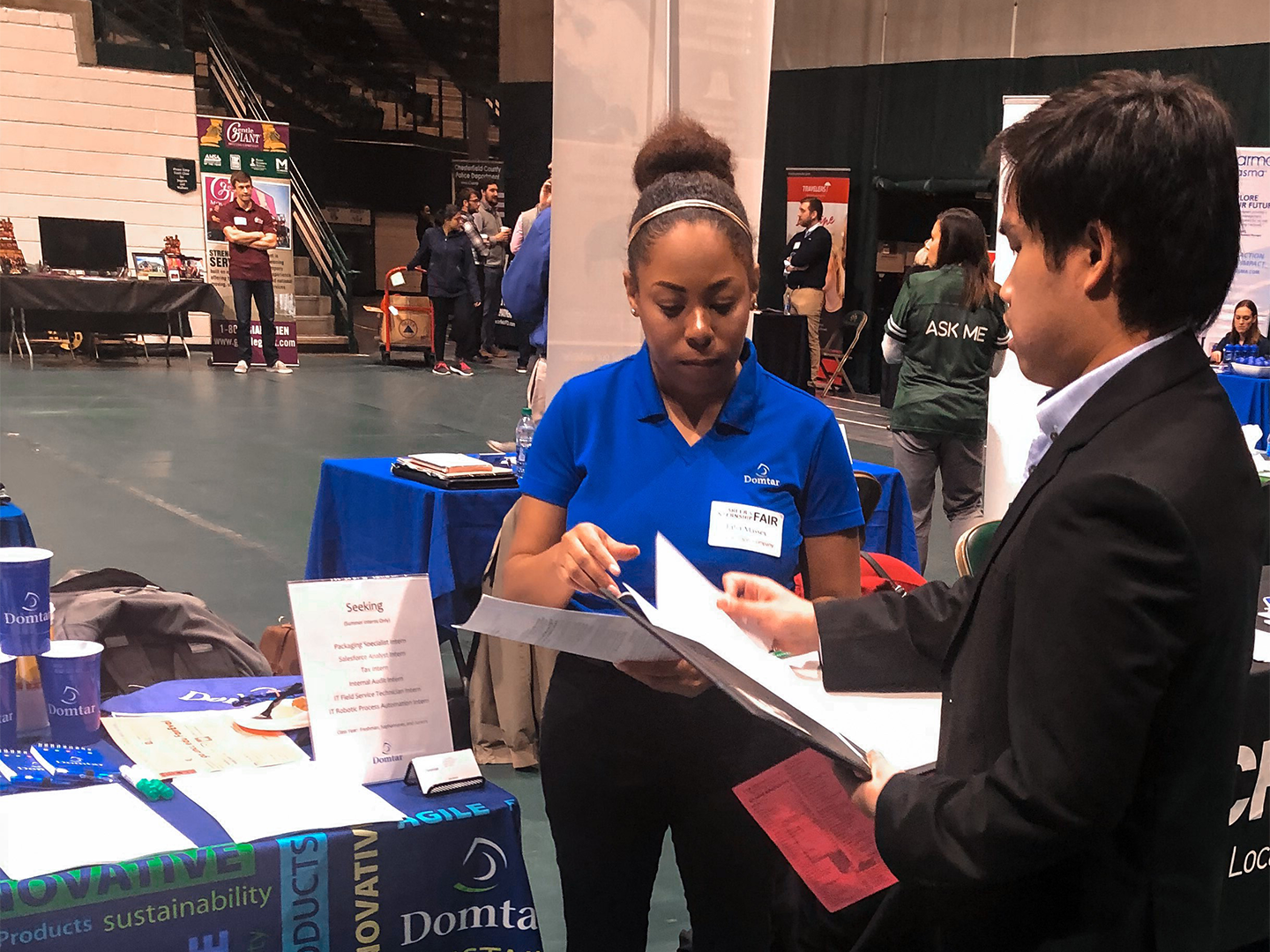 Talia Massey talks with a student at a college career fair in 2018. (Photo taken prior to COVID-19 pandemic.)